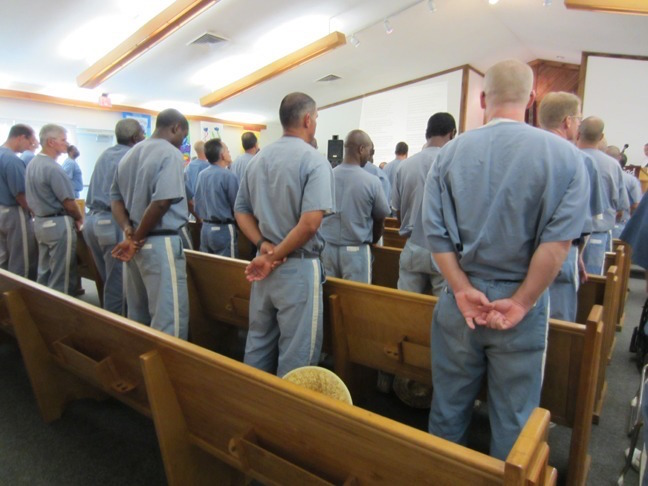 Chapel full of inmates attended a sermon.