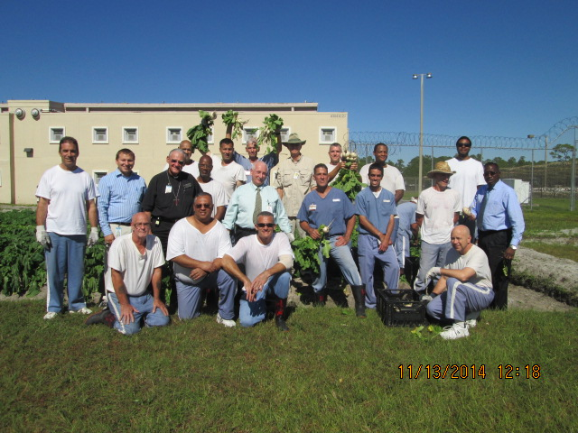 Group picture of inmates, Deacon, and other officials displaying the fruits of their labor.
