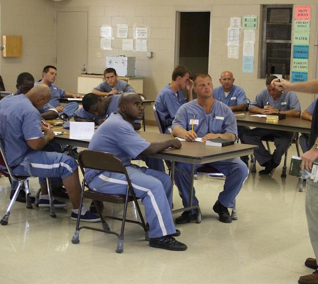 Inmates in a classroom setting, all with books and pencils, looking attentively at the instructor in the front of the room.