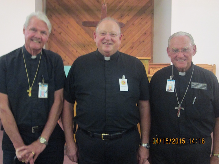 Three Deacons posing for a picture in front of a cross inside a church.
