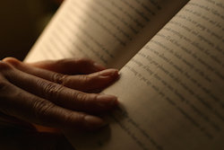 Person's hand holding a book open by the spine, text visible on the pages.