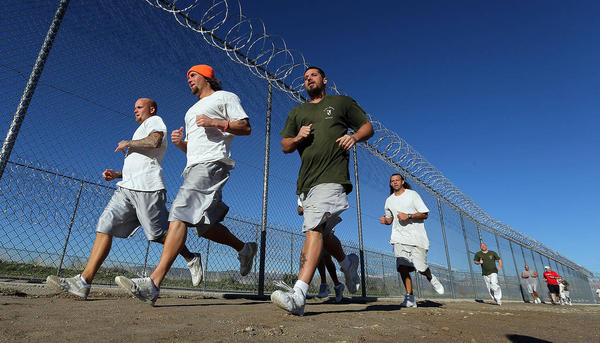 Inmates jogging along a razor wire fence.