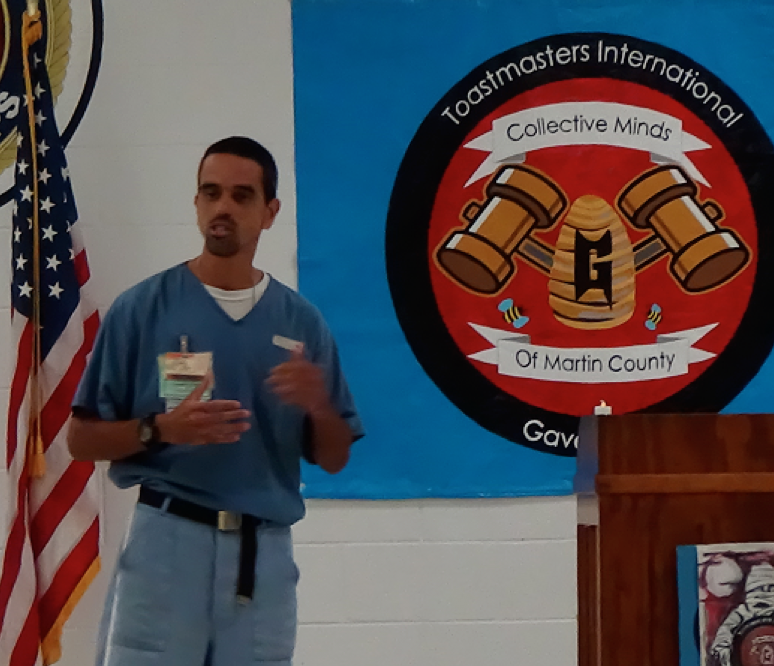 Inmate delivering a speech, the Toastmasters logo in the background.
