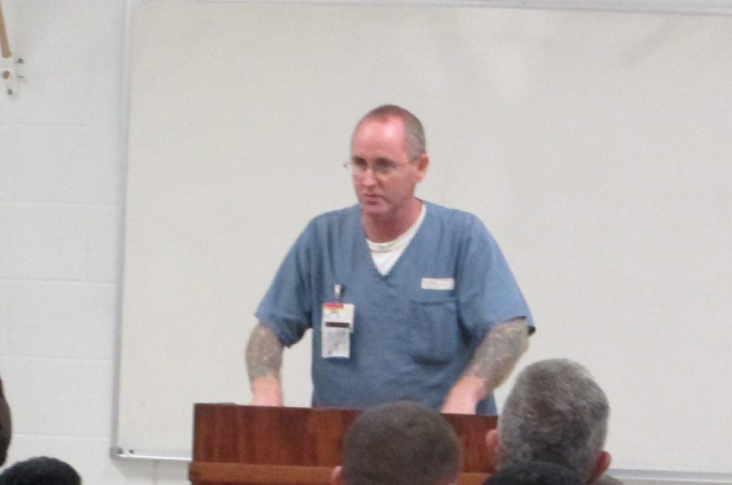 Inmate standing behind a podium delivering a speech.