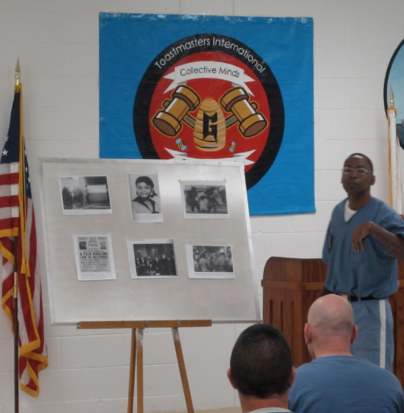 Inmate delivering a presentation, a board with pictures set up beside him, and the Toastmasters logo behind him.