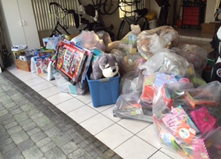 Massive jumble of toys in all different types of containers and bags delivered to a needy home.