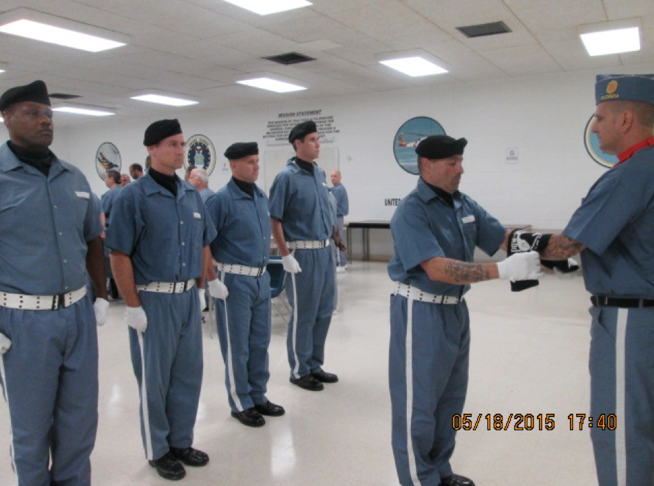 Several veterans dressed in blue and white, black berrets on their heads, and performing a ceremony.